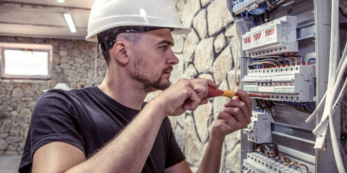 male-electrician-works-in-switchboard-with-an-electrical-connecting-cable